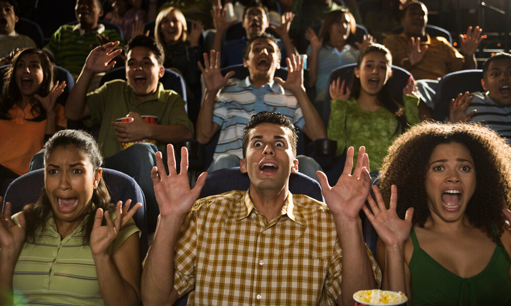 People reacting to scary movie in theater