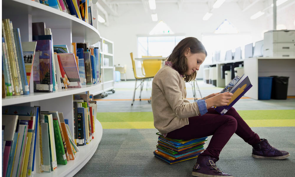 Girl sitting on stack of books reading in library
