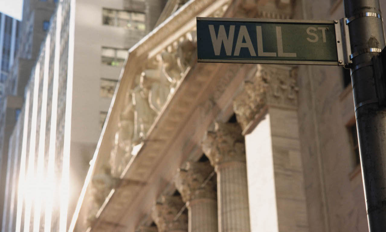 Street sign that reads Wall Street, in front of New York Stock Exchange building.