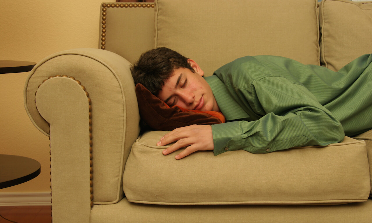 Young man sleeping on a couch.