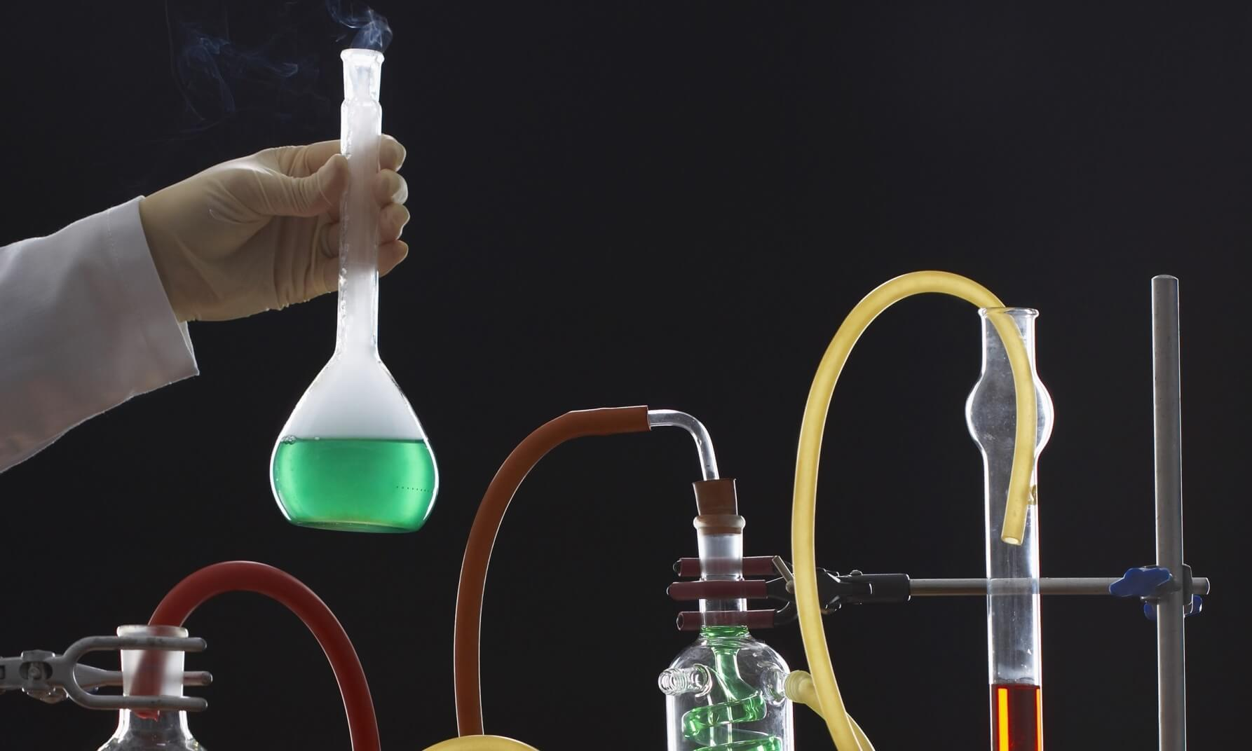 Hand holding flask above chemistry experiment