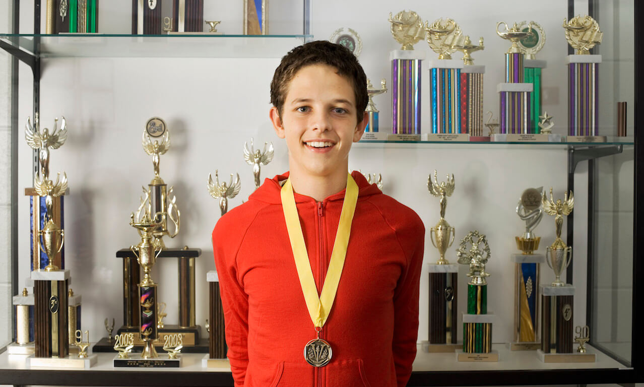 Teenage athlete wearing medal in front of trophy case
