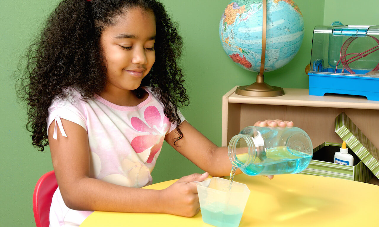 Girl pours water from a glass jar into a plastic measuring cup