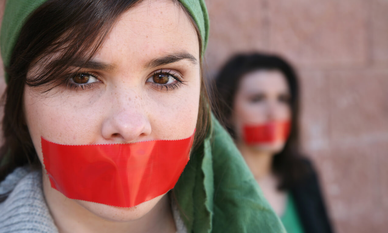 Woman wearing head scarf with red tape on her mouth