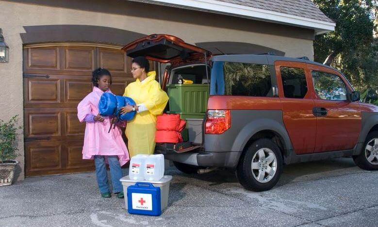 Family packing a car for an emergency evacuation on a cloudy day: mother and daughter in rain slickers