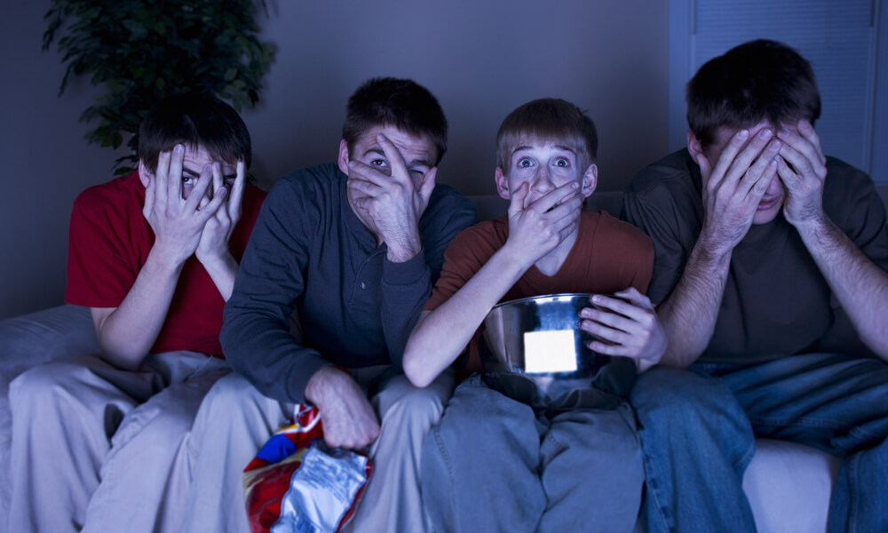 Four boys watching a scary show and eating popcorn