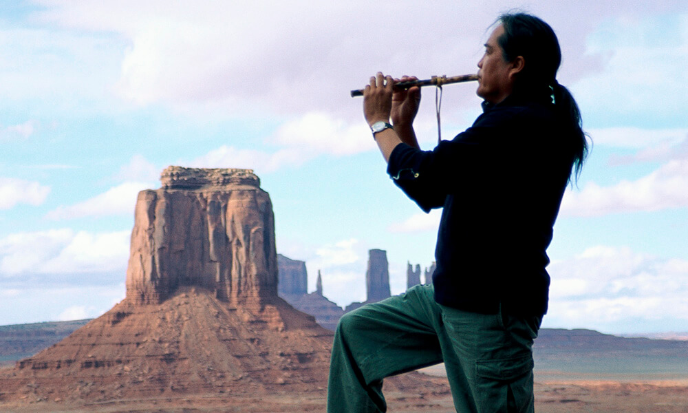 Native American man standing on a plateau and playing a flute-like instrument