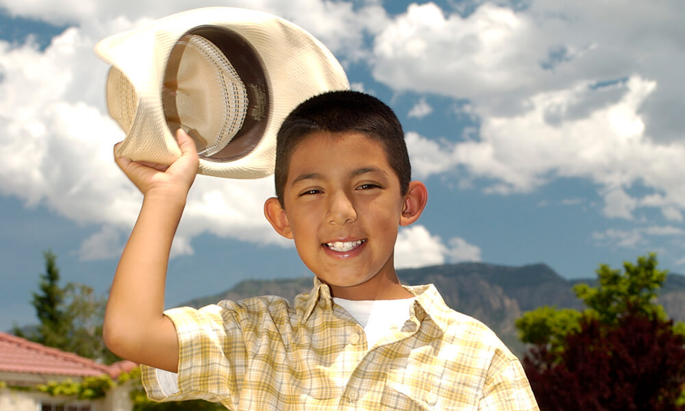 Hispanic boy holding a cowboy hat