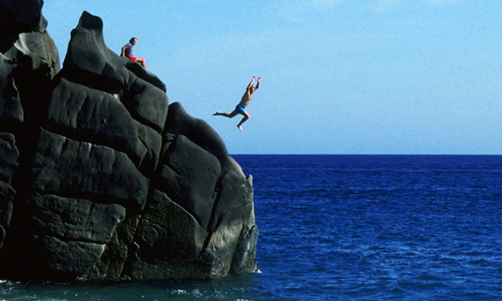 Young man jumping from rocky cliffs into the ocean