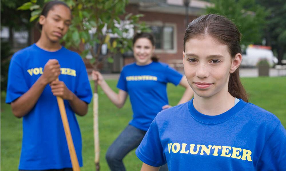 Portrait of teenage volunteers with shovels