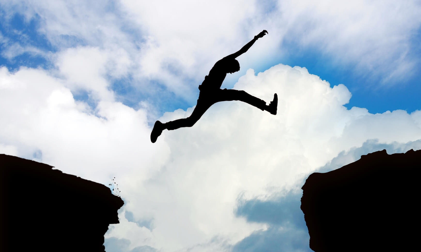 Silhouette of man jumping cliffs with cloudy sky