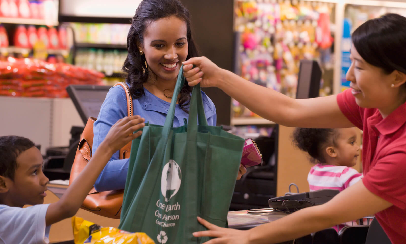 Mother and son using reusable bag in grocery store