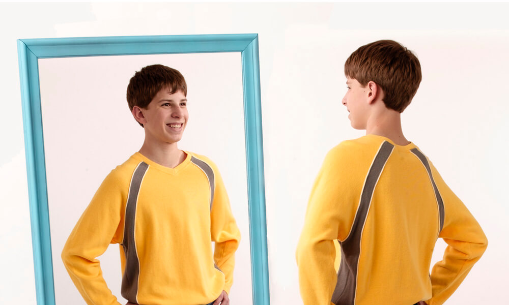 teen boy looking at himself in a mirror