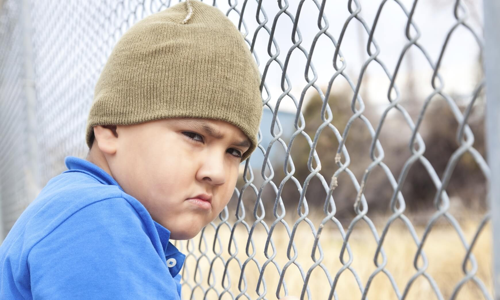 Upset young boy at a fence