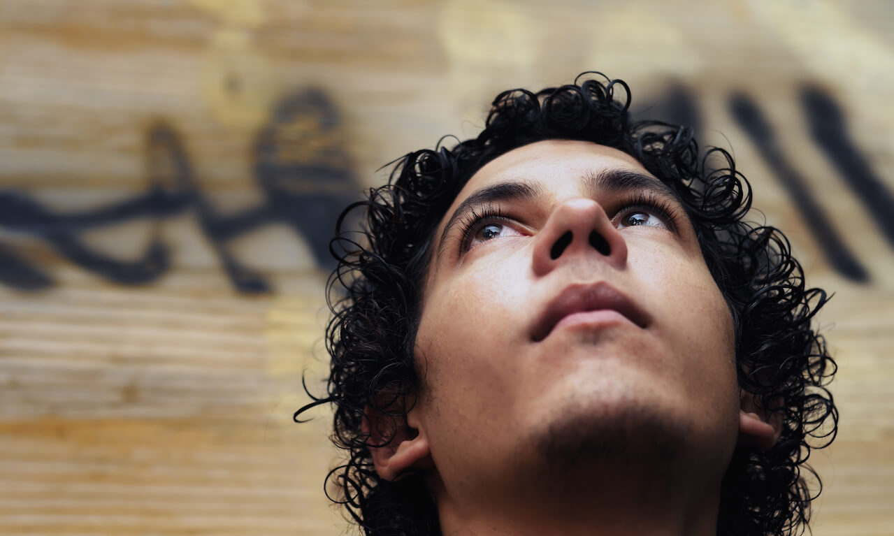 Young man looking up in front of grunge background