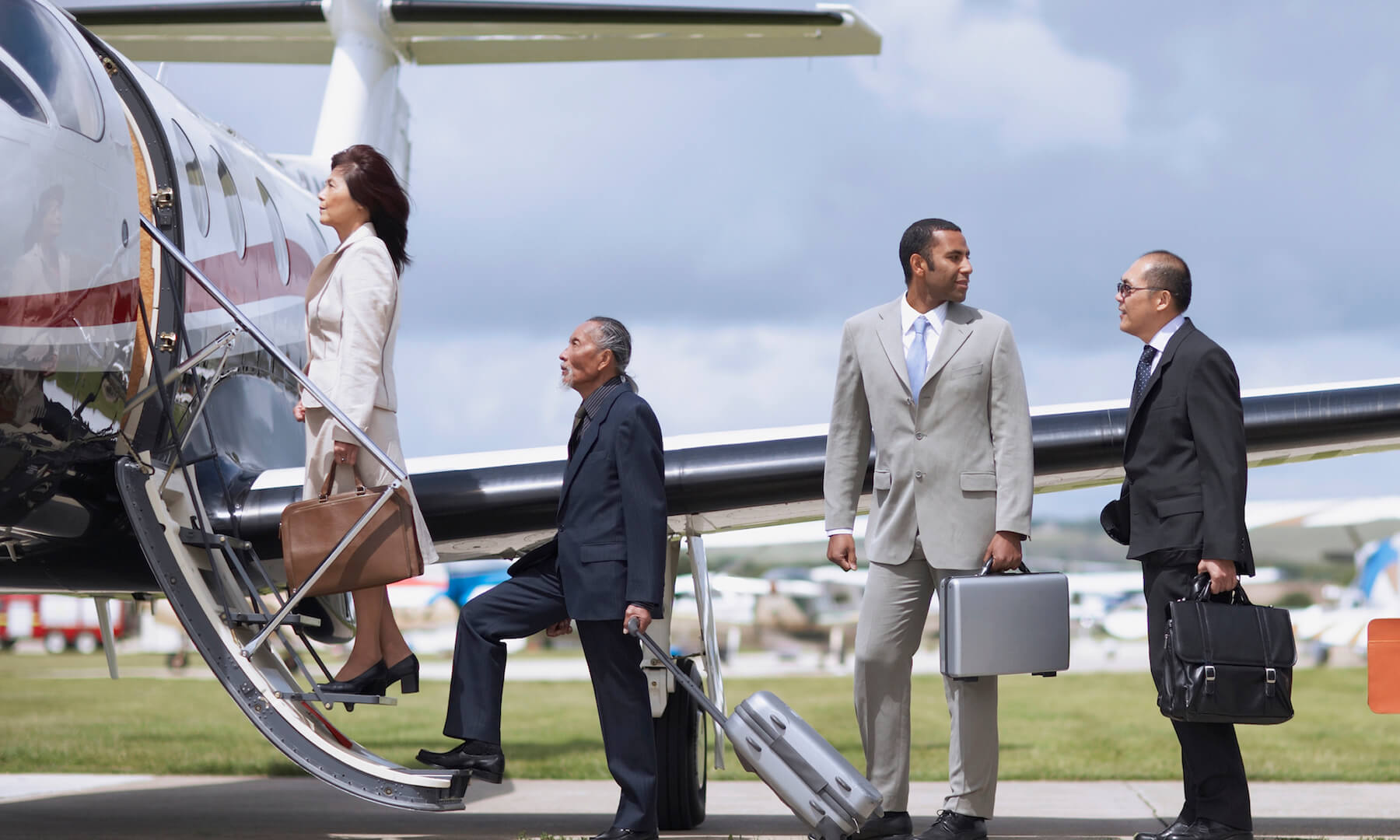 Businesspeople getting on airplane.