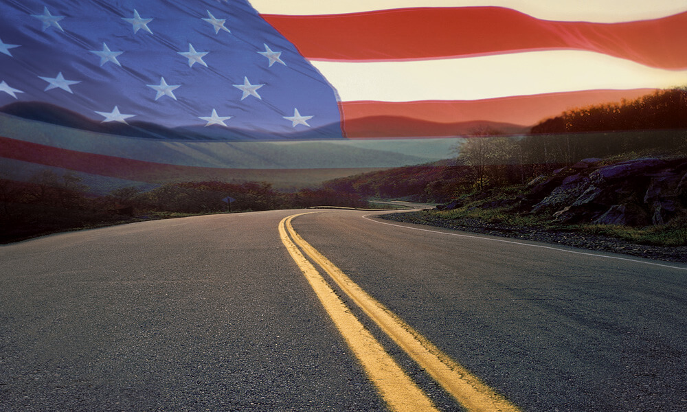 Road leading to American flag on the horizon