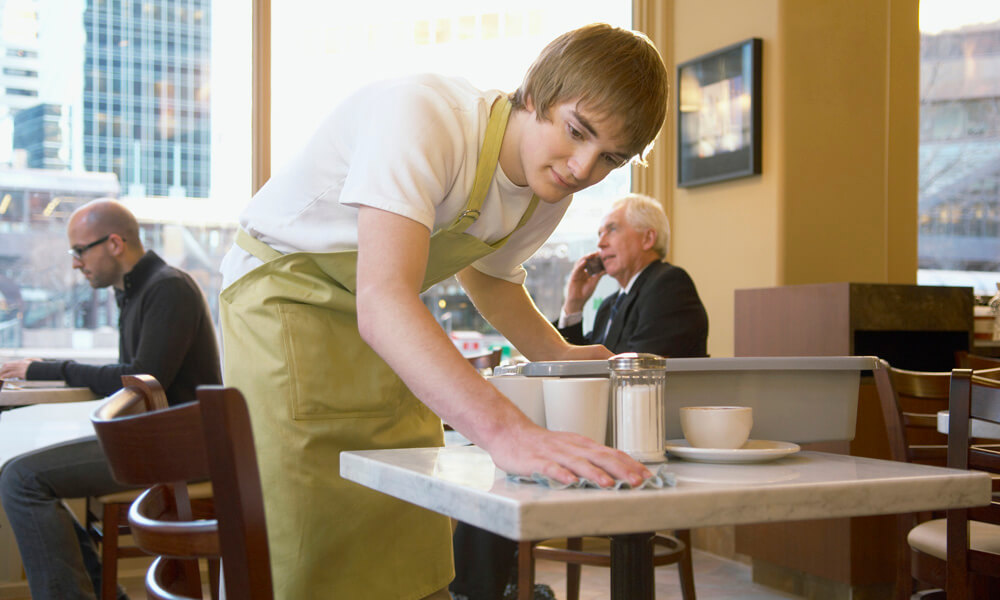 Busboy wiping table in coffee shop