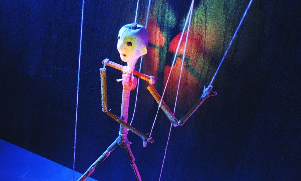 Puppet on stage with dramatic lighting