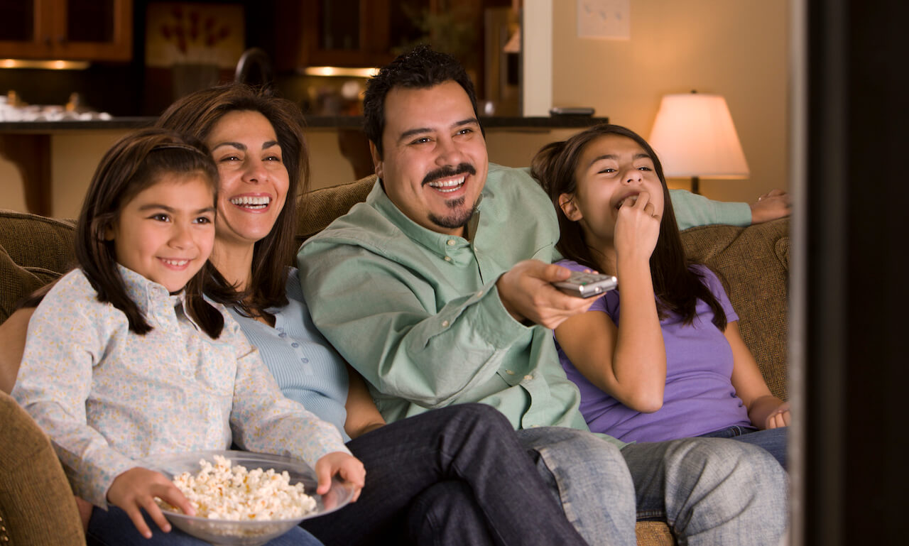 Hispanic family watching television together