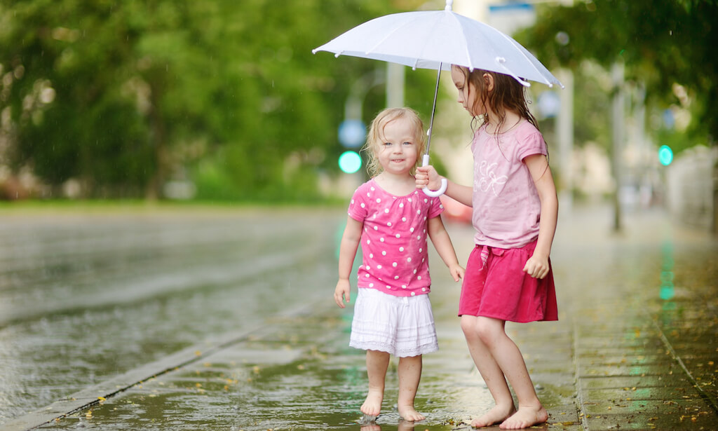 Barefoot sisters holding umbrella on a rainy summer day
