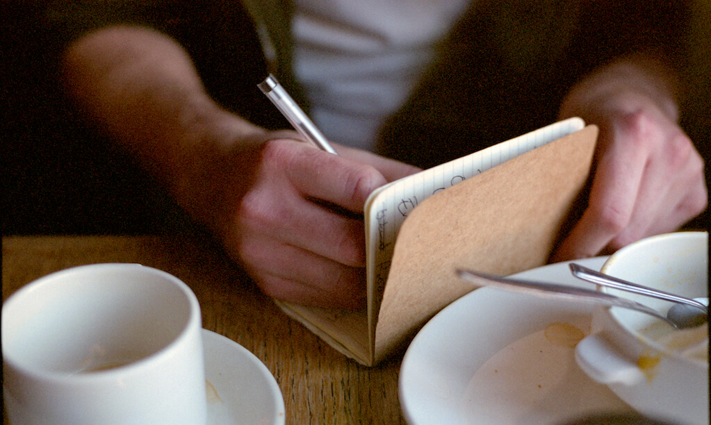 Close-up of man's hands as he writes in a noteboot at a cafe, surrounded by tableware