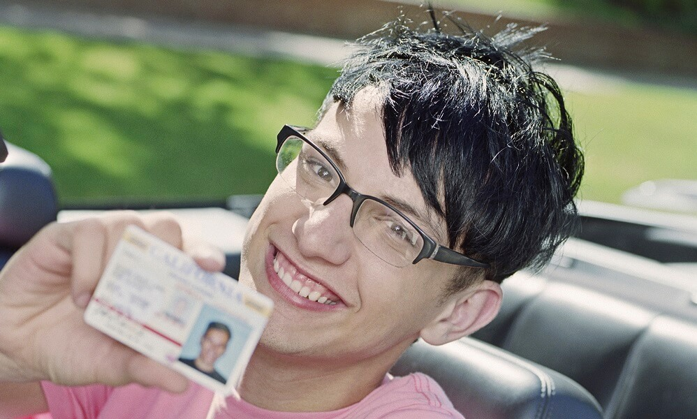 Teen driver holding new license and smiling