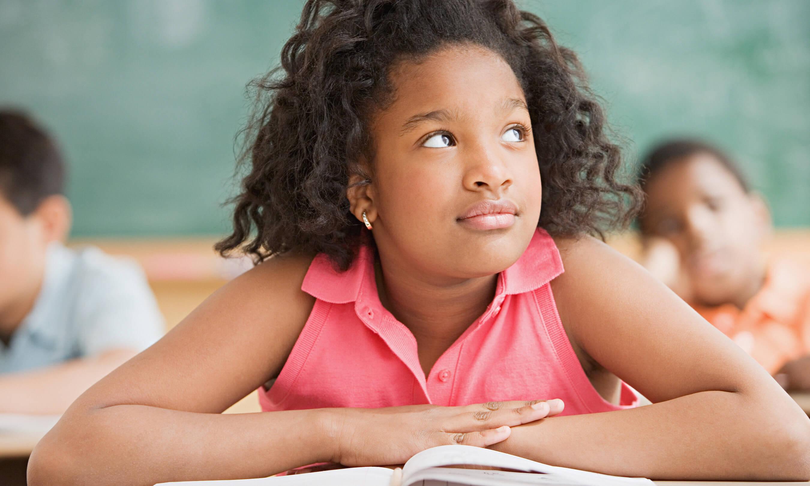 Schoolgirl daydreaming in classroom