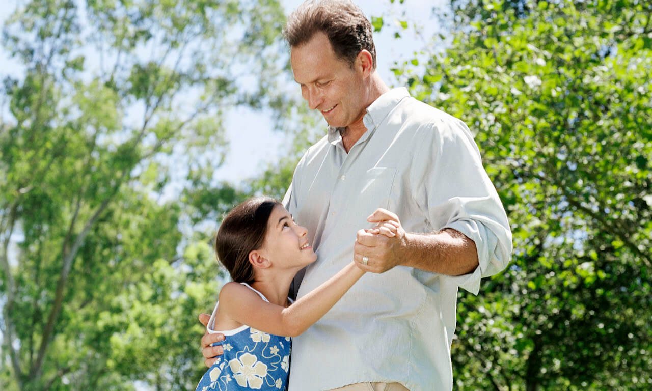Father dancing with daughter outside