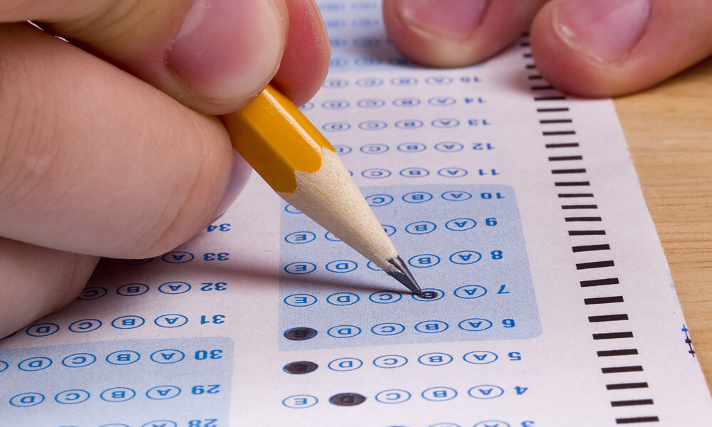 Student filling out test form with a pencil