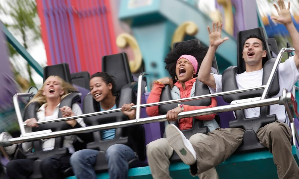 Blurred motion of four people on fairground ride, screaming