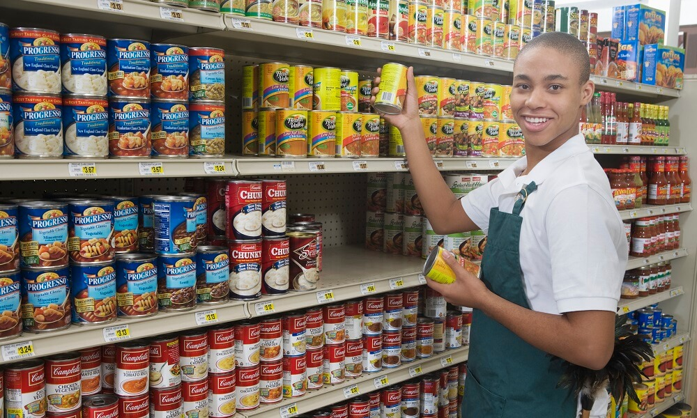 Teenage supermarket employee (16-19 years old) stocking shelf, smiing over shoulder