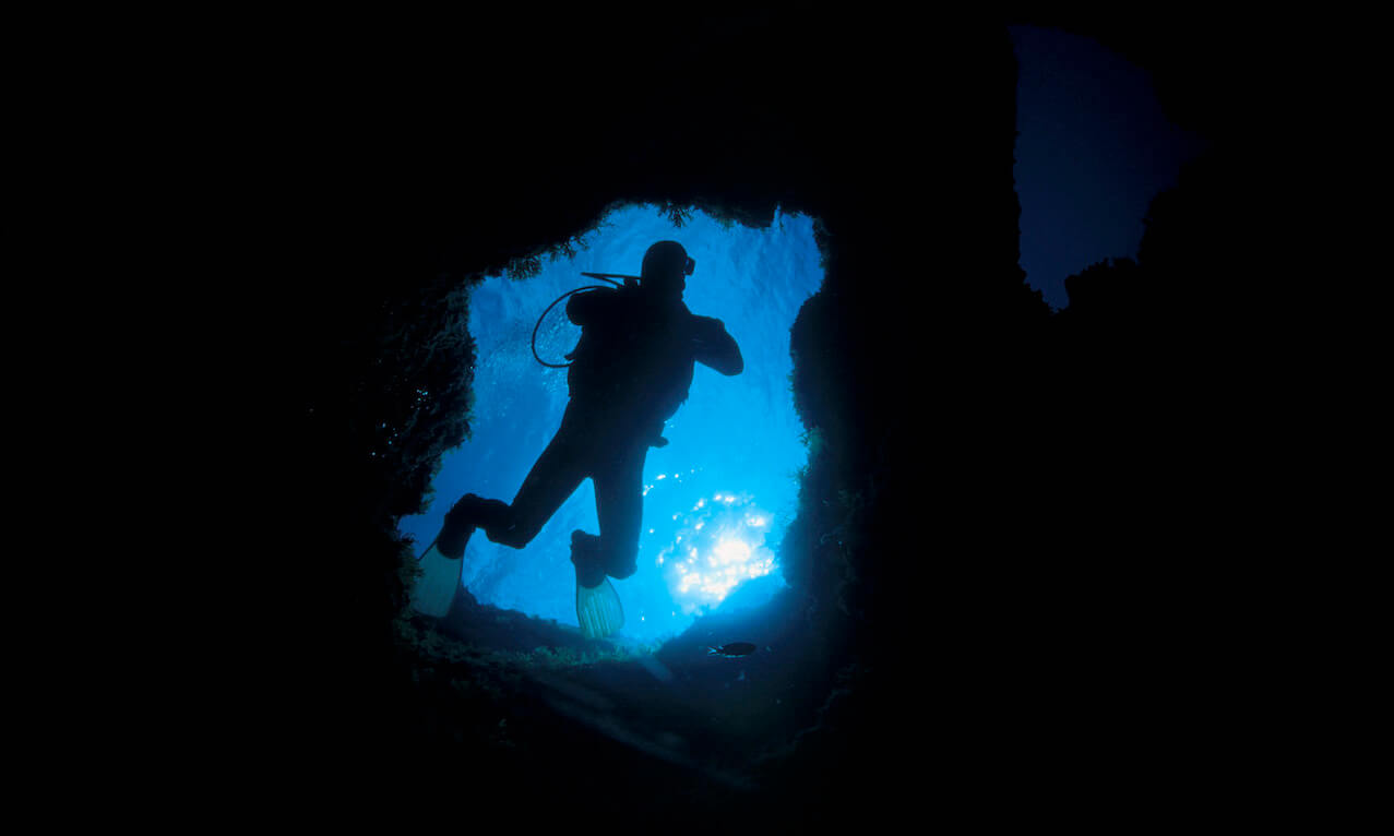 Scuba diver entering an undersea cave