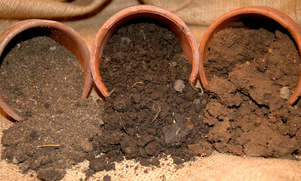 Three terracotta pots on side with soil spilling out: sandy soil, loamy soil, and clay soil