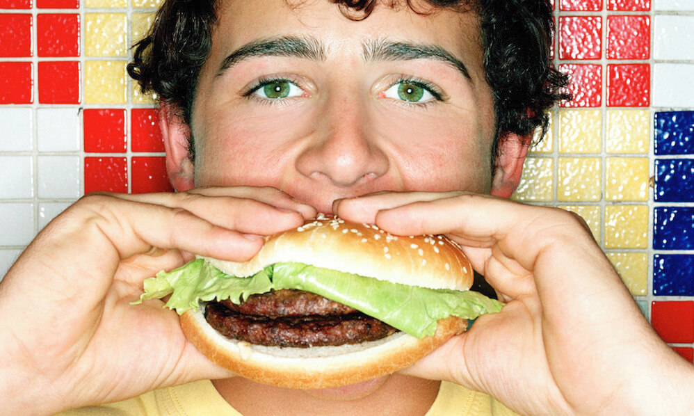 Young man eating a double hamburger
