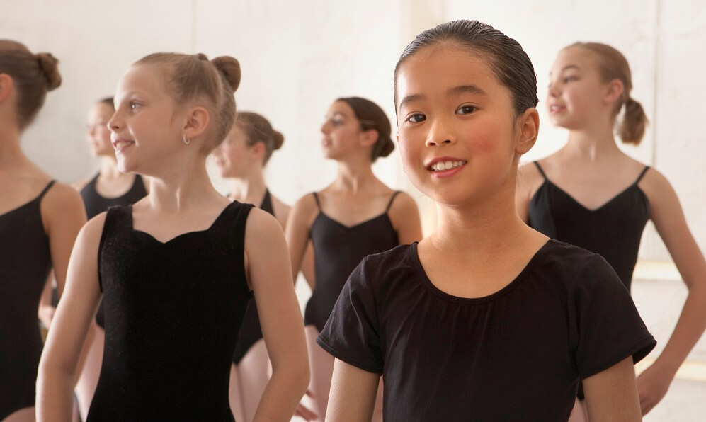 Girls (9-13 years old) in ballet class, girl in foreground smiling