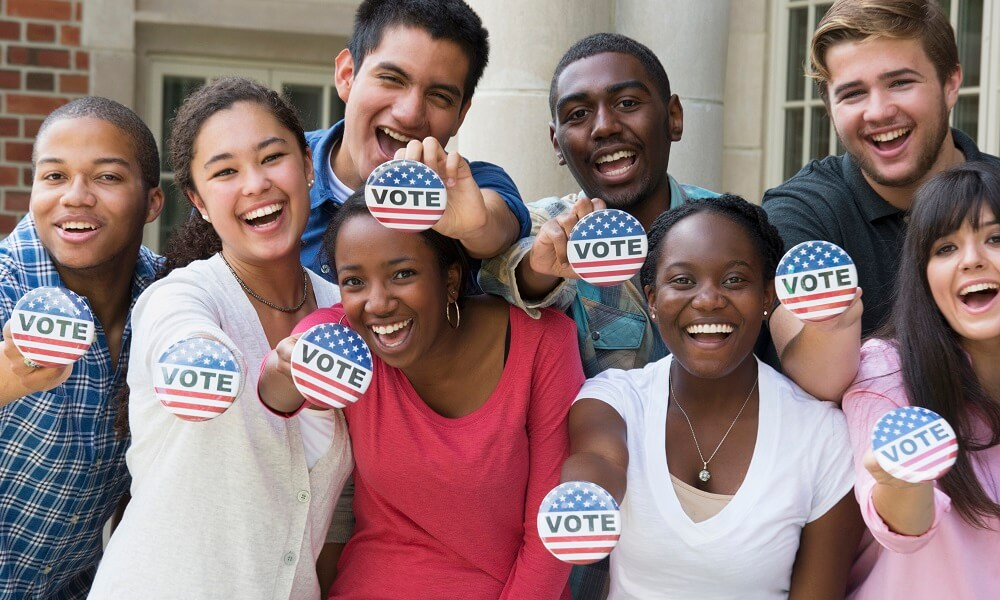 Students holding buttons encouraging voting