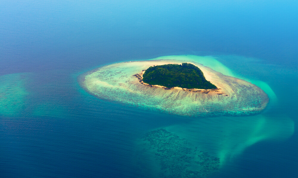Aerial view of tropical island surrounded by sea water in various shades of blue