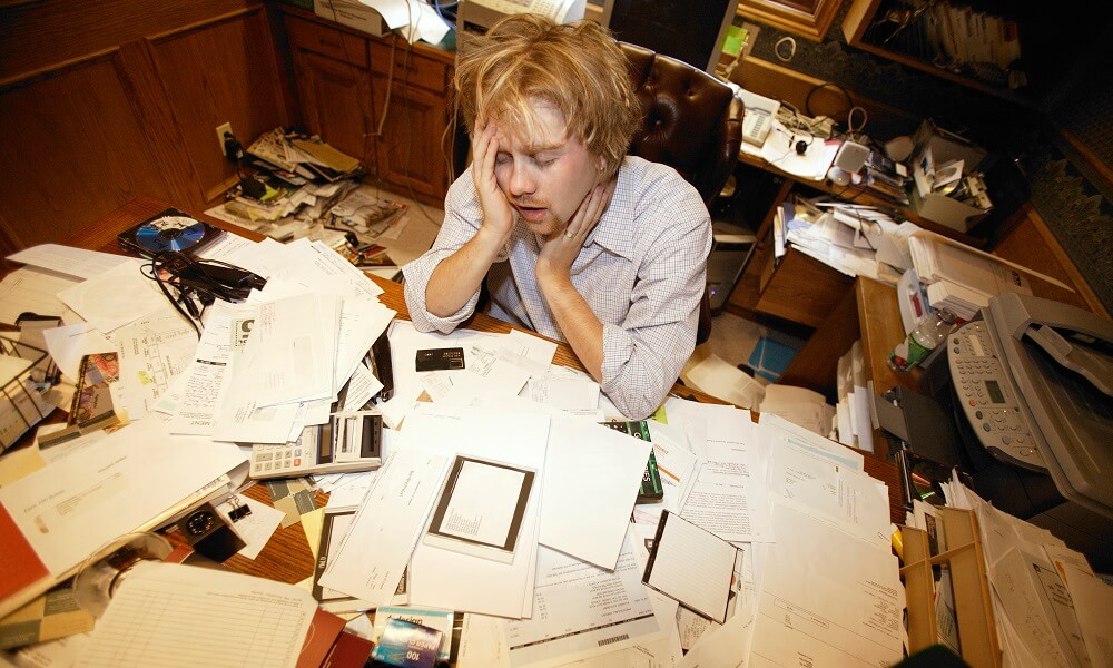 Man asleep at desk with piles of paperwork