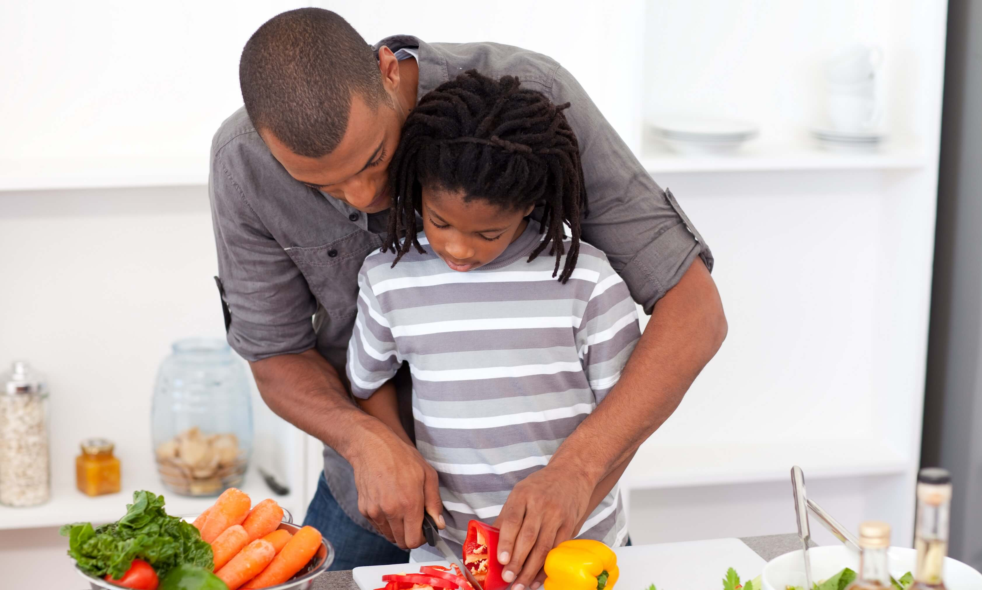 Father and son cutting vegetables for a salad