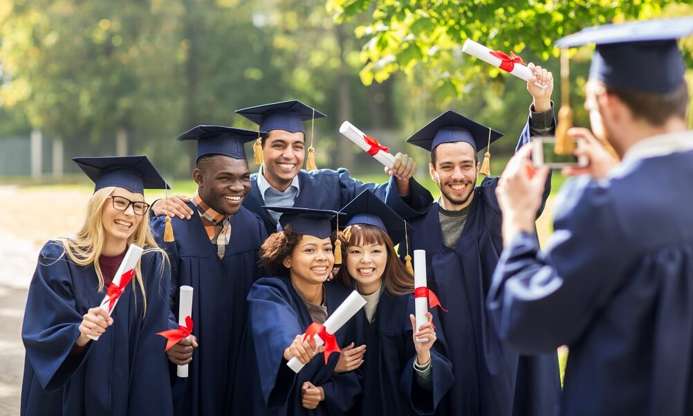 Group of happy graduates wearing traditional caps and gowns and holding diplomas posing for a photo