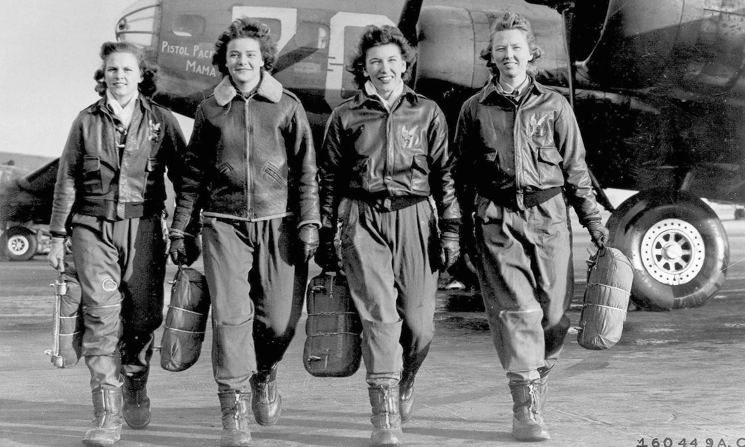Four female pilots pose in front of a military aircraft