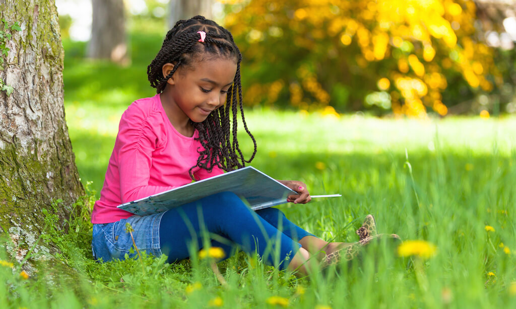 Outdoor portrait of a cute young black little girl reading a book