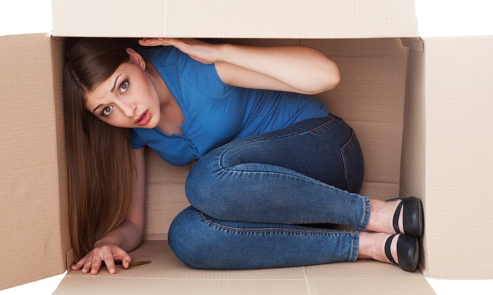 Young woman in cramped cardboard box