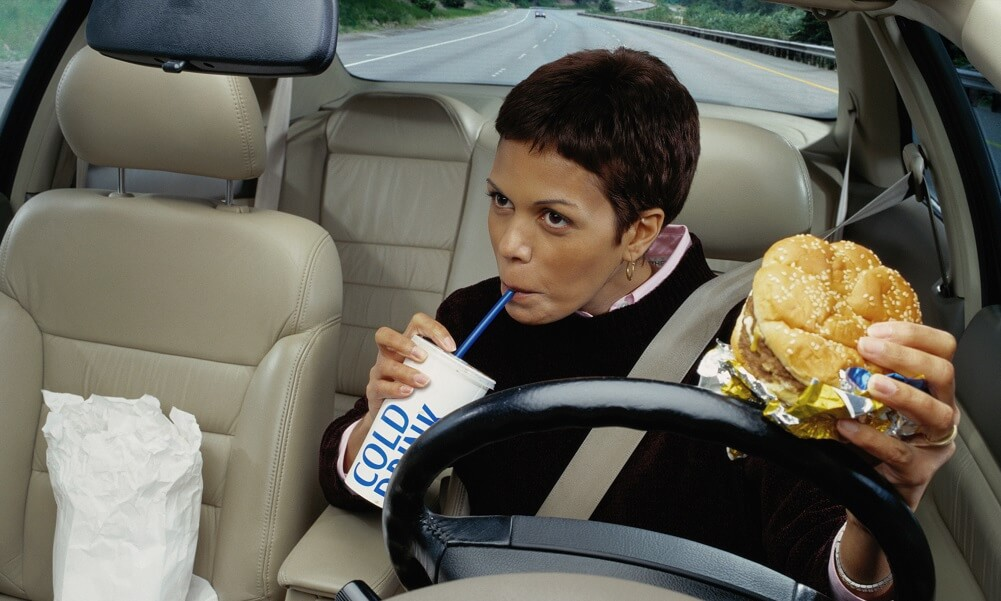 Distracted driver: Woman eating fast food while dr