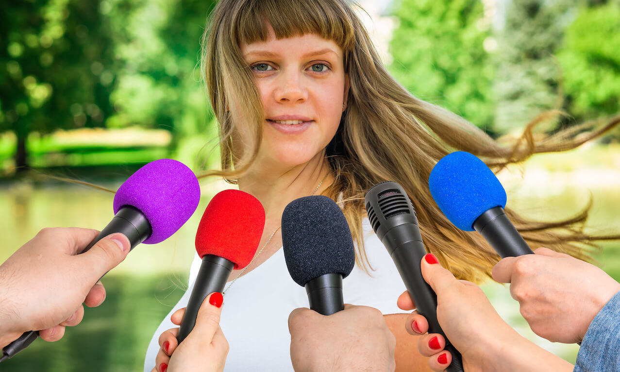Reporters with microphones making interview with young woman - journalism and broadcasting concept