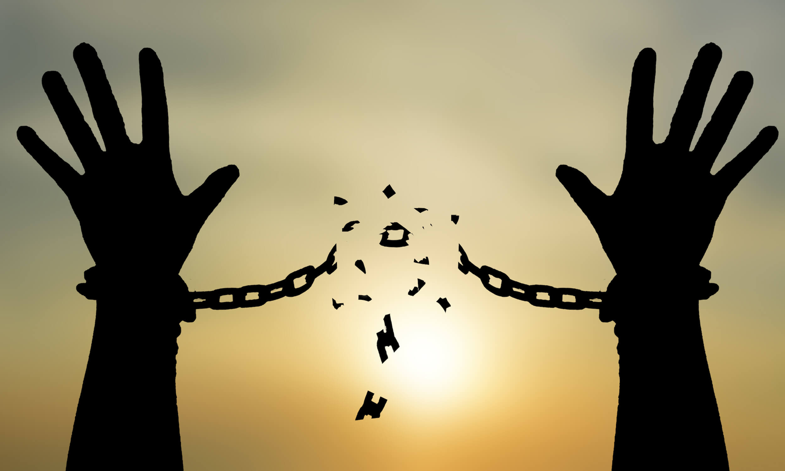 Silhouette of human hands breaking out of chains