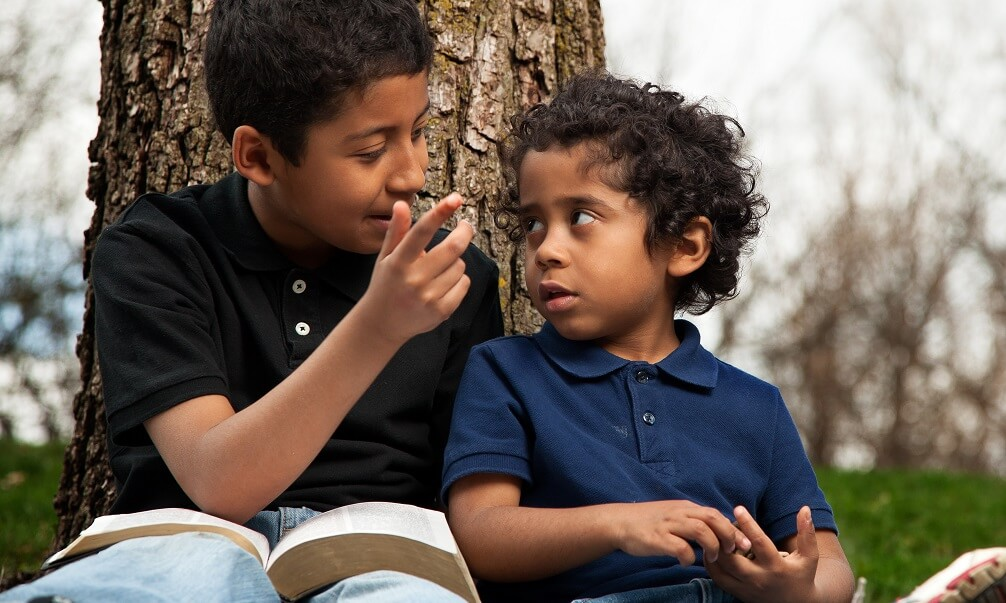 Young boys reading a book and talking outside, leaning against a tree