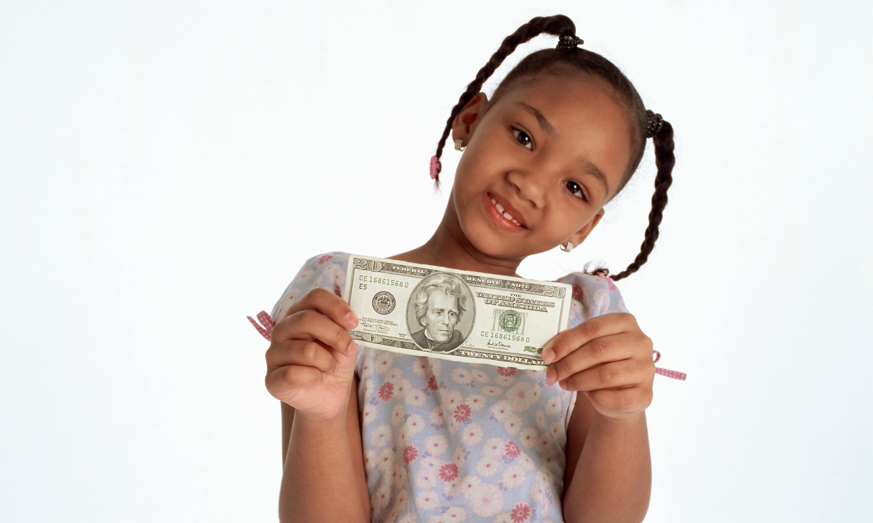 Young girl showing the face of a twenty dollar bill