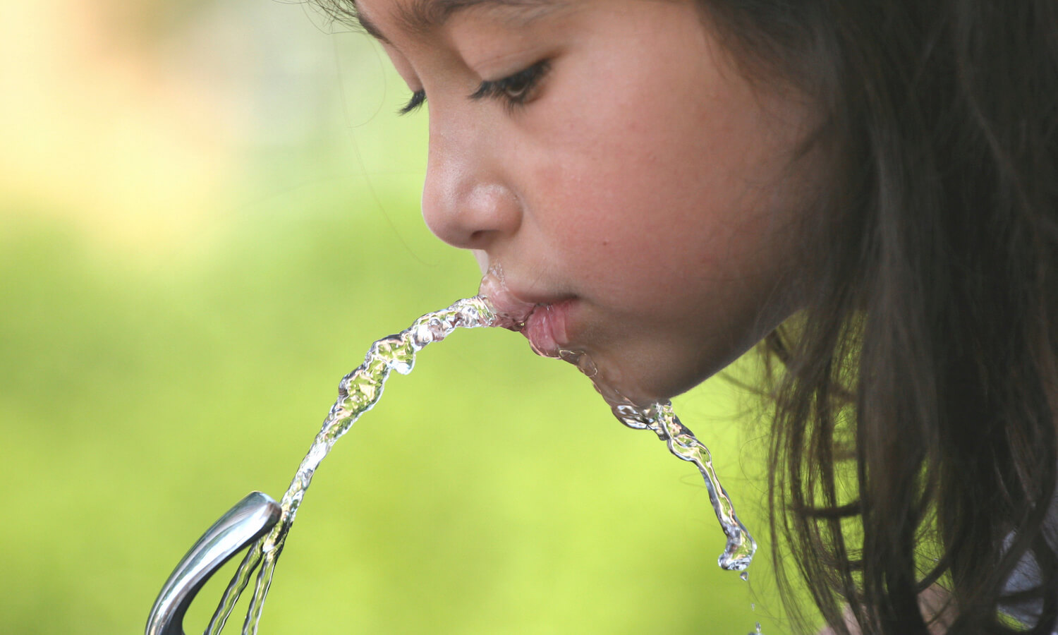 Girl drinking from a water fountain